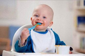 ребенок до года учится есть  играя